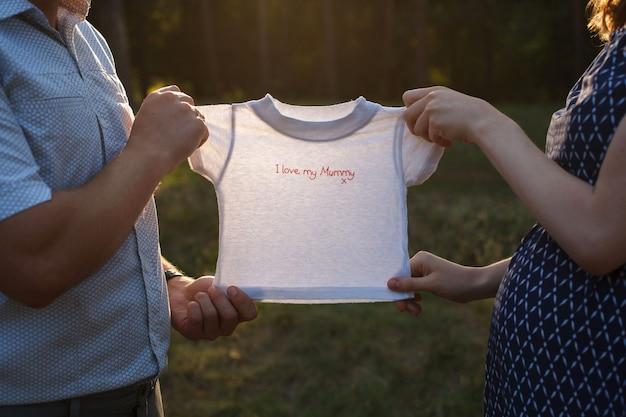 健康な妊娠の9ヶ月をクローズアップ。妊娠中の若い女性と彼女の夫は屋外で生まれたばかりの赤ちゃんのための服を保持しています。碑文「私は私のお母さんが大好きです」。春の自然の中を歩いて幸せな妊娠中のカップル