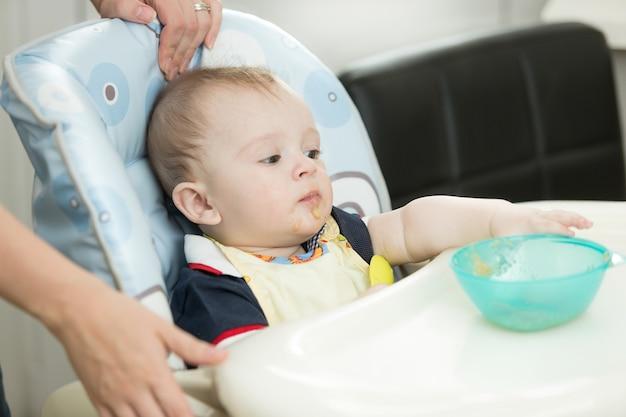 9-месячный мальчик сидит в детском стульчике и тянется к тарелке