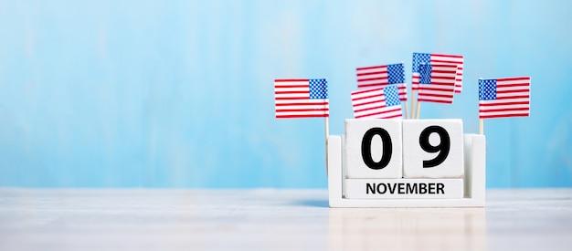 木材にアメリカ合衆国の国旗と白いカレンダーの11月9日