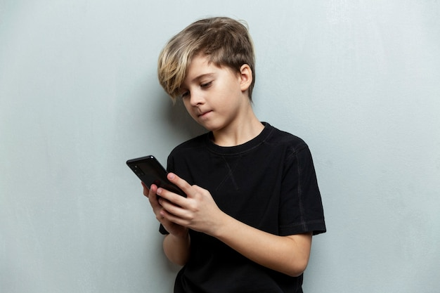 A 9-year-old boy in a black t-shirt stands with a phone