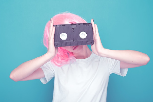 90's fashion. girl with cassette standing isolated in a blue background.