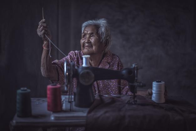 ヴィンテージミシンを使用しているかわいい90歳のシニア女性。
