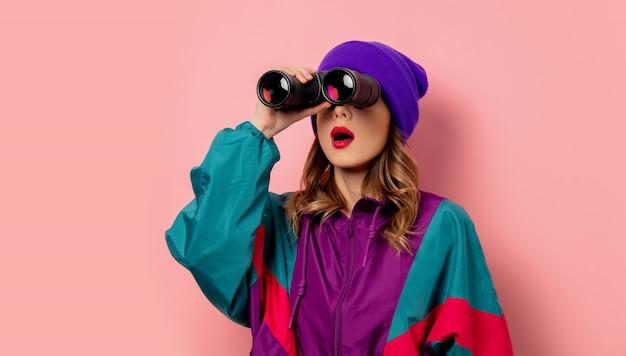 ピンクの壁に双眼鏡で紫の帽子と90年代の服の若い女性