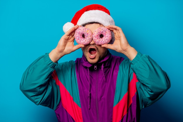 Красивый мужчина в новогодней шапке и куртке 90-х с пончиками