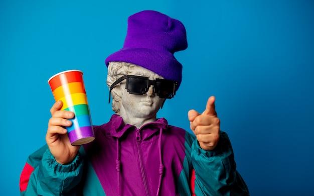 90年代の流行の服に身を包んだアンティークの像は一杯の飲み物を保持します