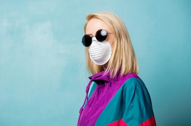 フェイスマスクと90年代スタイルの服の金髪の女性