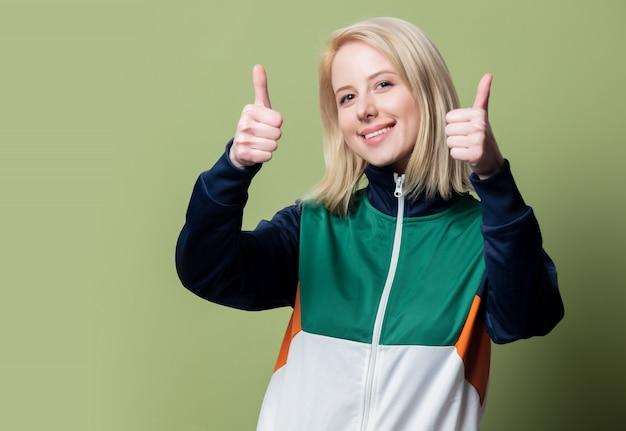 Красивая блондинка в спортивном костюме 90-х показывает жест ок