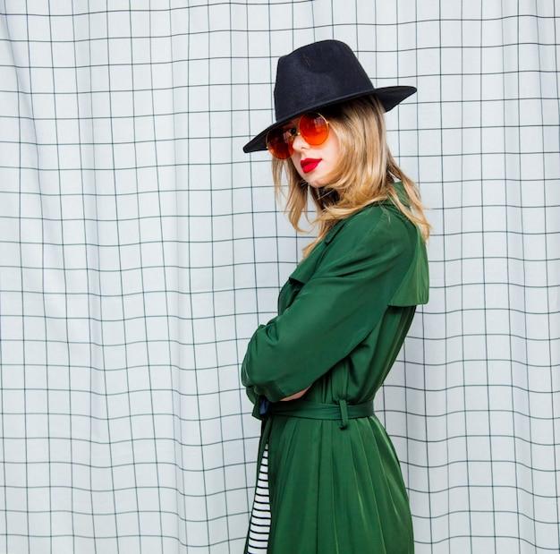 サングラスと90年代スタイルの緑のマントの若いスタイルの女性