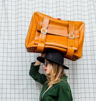 旅行スーツケースと90年代スタイルの帽子と緑のマントの女性