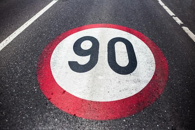 アスファルト道路に描かれた90km / hの制限速度標識。