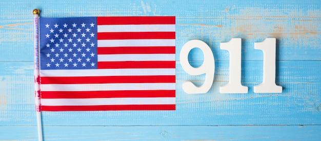 木製のテーブルの背景に911のテキストとアメリカ合衆国の旗。愛国者の日、9月、記念と決して忘れないコンセプト