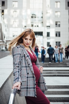 Беременная девушка блондинка в бордовом платье. в большом городе. вред для окружающей среды. длинные волосы. 9 месяцев в ожидании. небоскребы. толпа людей. раздражение. счастье быть мамой. толпа и раздражение.