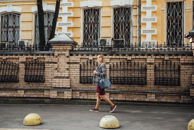 カジュアルなスタイルで金髪の妊娠中の女の子。バーガンディのドレスとグレーのジャケット。フィットしてください。大都市で。長い髪。 9ヶ月待っています。母になる幸せ。健康状態を監視します。旧市街の背景について。