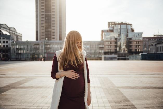 Беременная девушка блондинка в бордовом платье. в большом городе. вред для окружающей среды. длинные волосы. 9 месяцев в ожидании. небоскребы. градостроительство. счастье быть мамой. одиночество. мать-одиночка.