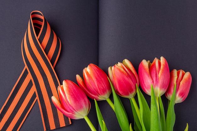 Шаблон пустой открытки на 9 мая. красные цветы (тюльпаны), георгиевская ленточка на черной тетради. день победы или день защитника отечества концепции. вид сверху, скопируйте пространство для текста