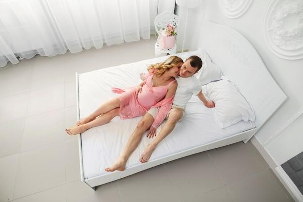 Молодая счастливая семья ждет ребенка. муж нежно обнимает беременную жену в спальне. улыбающаяся беременная пара в спальне. 9 месяцев беременности