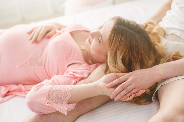 Молодая счастливая семья ждет ребенка. муж нежно обнимает беременную жену в спальне. женщина в ожидании рождения ребенка крупным планом. 9 месяцев беременности
