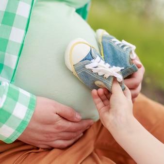 晴れた日に屋外散歩のための妊娠中の女性と彼女の長女の肖像画。幸せな母性の概念。健康妊娠概念の9ヶ月をクローズアップ。妊娠中の腹に新生児用の靴