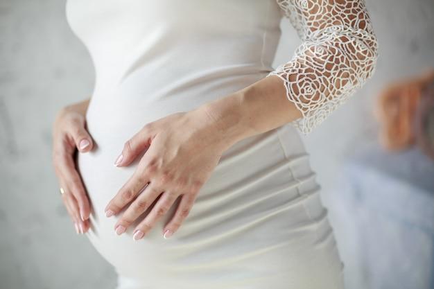 白いドレスを着た美しい妊娠中の女性の肖像画は、お腹に優しく触れますをクローズアップ。若い女の子は彼女の腹を抱き締めます。白で分離された9ヶ月の健康妊娠。出産を見越して女性