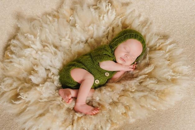 生まれたばかりの赤ちゃんの男の子、生後9日、寝ていて、緑の衣装とベージュ色の背景に包まれています。