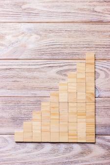 追加のテキストのタイトルを追加するためのコピースペースを持つ黒い木製テクスチャ背景の上の木製のブロックキューブ。概念または概念のウッドブロックの階段または9つのステップ。キュービック