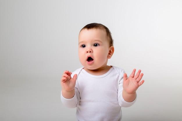 Малыш 9 месяцев в белом боди сидит на белой стене