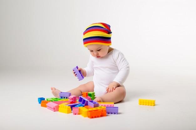 白い壁にマルチカラーコンストラクターで遊んで9ヶ月の男の子
