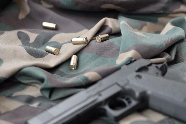 Пули калибра 9 мм и пистолет лежат на сложенной камуфляжной зеленой ткани. набор предметов для стрельбища или комплект для самообороны. золотые патроны возле пистолета