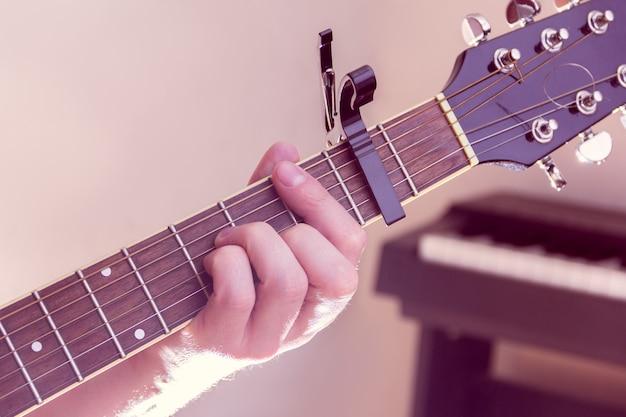 男の手がギターを弾く