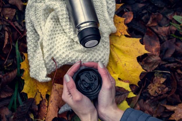 女性の手と魔法瓶の熱いお茶