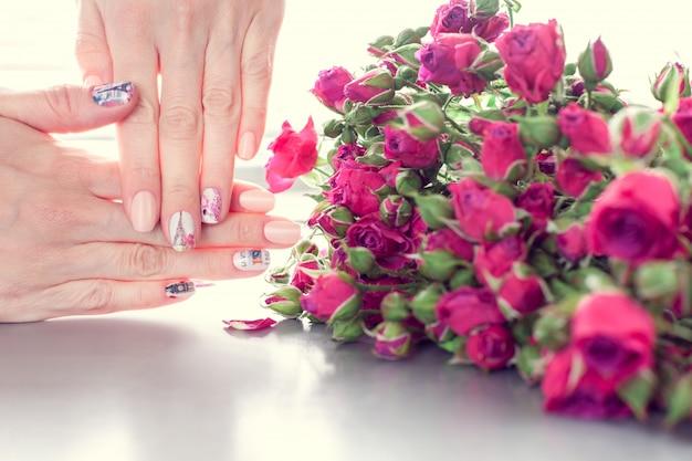 アートネイルマニキュアと小さなピンクのバラの女性の手