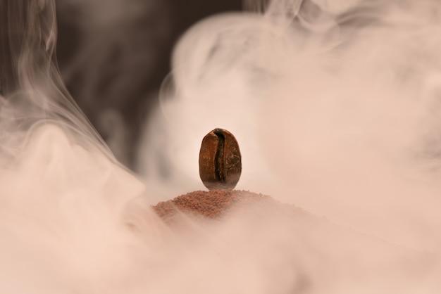 新鮮な焙煎コーヒー豆が煙の中で挽いたコーヒーの散乱の上に立つ