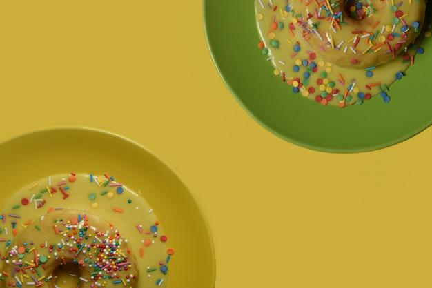 Половина пончика с желтой глазурью на зеленом блюде плюс половина пончика с желтой глазурью на желтой тарелке