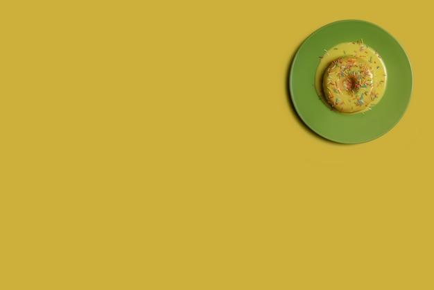 Пончик с желтой глазурью и разноцветной пудрой на зеленой тарелке.