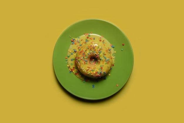 Пончик с желтой глазурью и разноцветной пудрой на зеленом блюде.