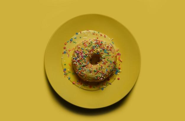 Пончик с желтой глазурью и разноцветной пудрой на желтой табличке.