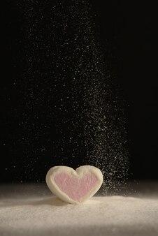 Сердце зефиров на черной предпосылке в напудренном сахаре.