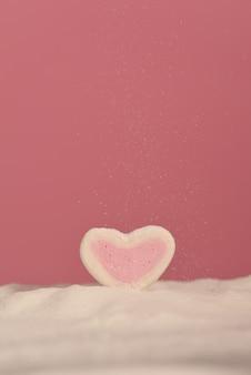 Сердце зефиров на розовой предпосылке в напудренном сахаре.
