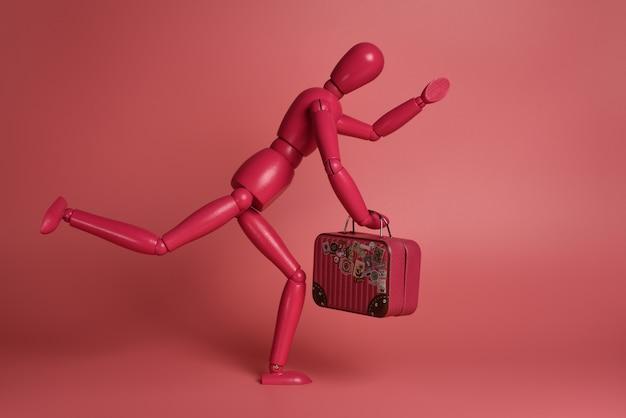 Розовый деревянный человечек с чемоданом бежит на розовом фоне