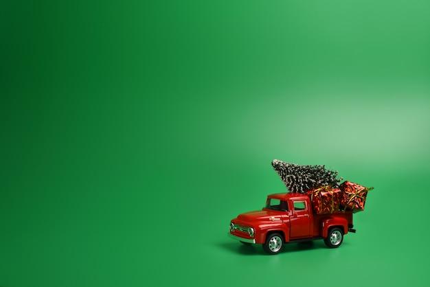孤立した緑の背景の後ろにクリスマスツリーと赤いピックアップトラック