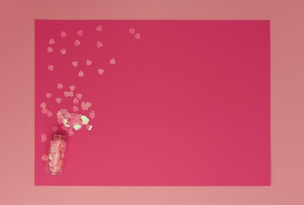 Блестящие розовые сердечки упали на ярко-розовую рамку из фактурной бумаги