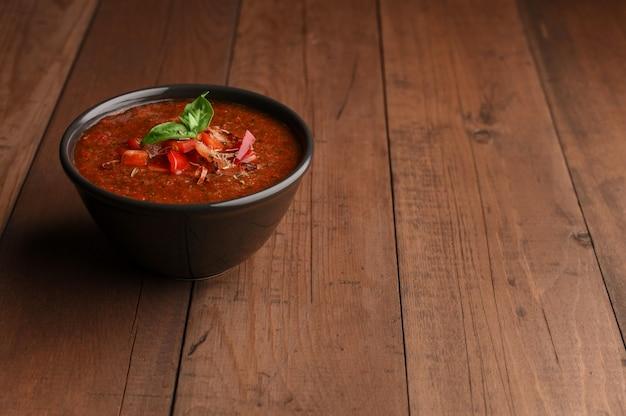 木製のテーブルにバジルのスパイシーな自家製ガスパチョスープ。テキストのための場所が付いているボールの夏トマト冷たいスープ。