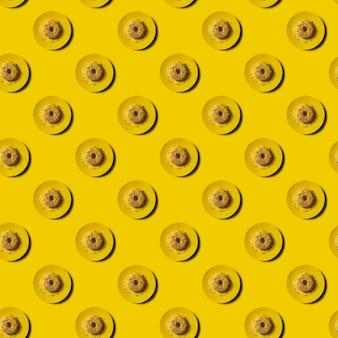 黄色の背景のシームレスな繰り返しパターンにドーナツと黄色のプレート。モノクロのお菓子のパターン。黄色いプレートに黄色いレモン釉薬のおいしいドーナツ。