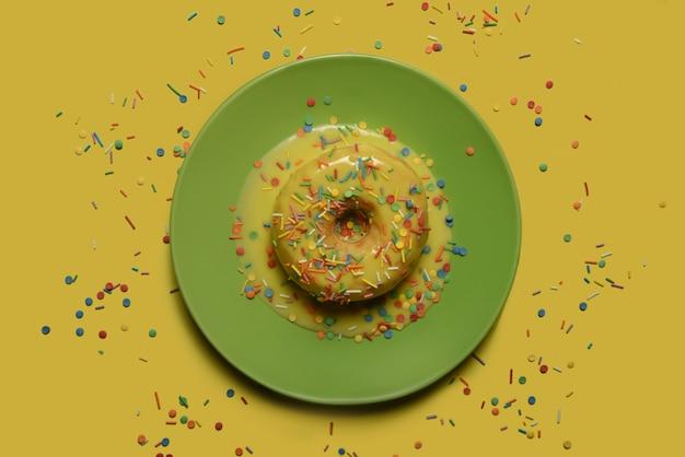 Пончик с желтой глазурью и разноцветной пудрой на зеленом блюде