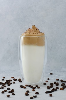 コーヒー豆とチョコレートで飾られた背の高いグラスのダルゴナコーヒー。明るい背景にコーヒーの泡と泡状のラテ。