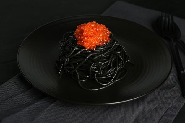 暗い背景に黒皿に赤キャビア添えイカ黒パスタ。シーフードの黒スパゲッティ。