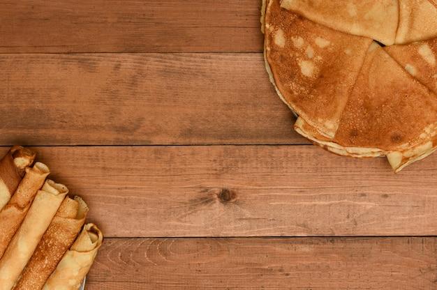 木材の背景上面に薄いパンケーキを折りたたみます。朝食のパンケーキ。