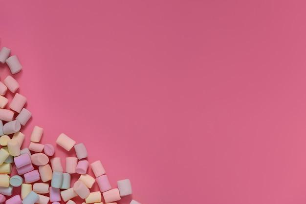 ピンクの背景の角に散在している孤立した色とりどりのマシュマロ