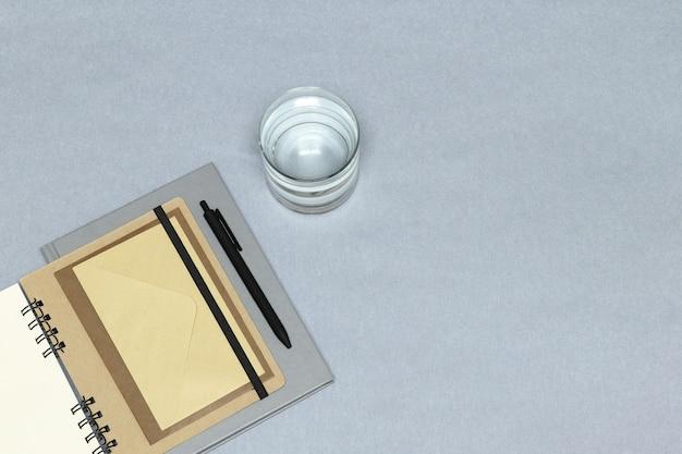 Блокноты, черная ручка, конверты, стакан воды на сером фоне