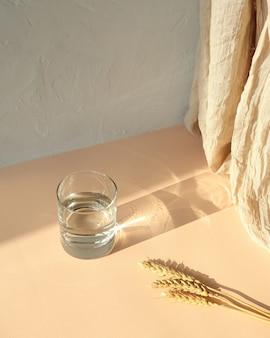 小麦、影とベージュのテーブルの上の水のガラス